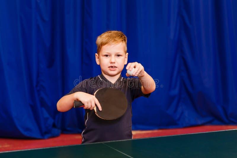 Ein Kind mit einem Ball und einem Tischtennisschläger untersucht die Kamera lizenzfreies stockfoto