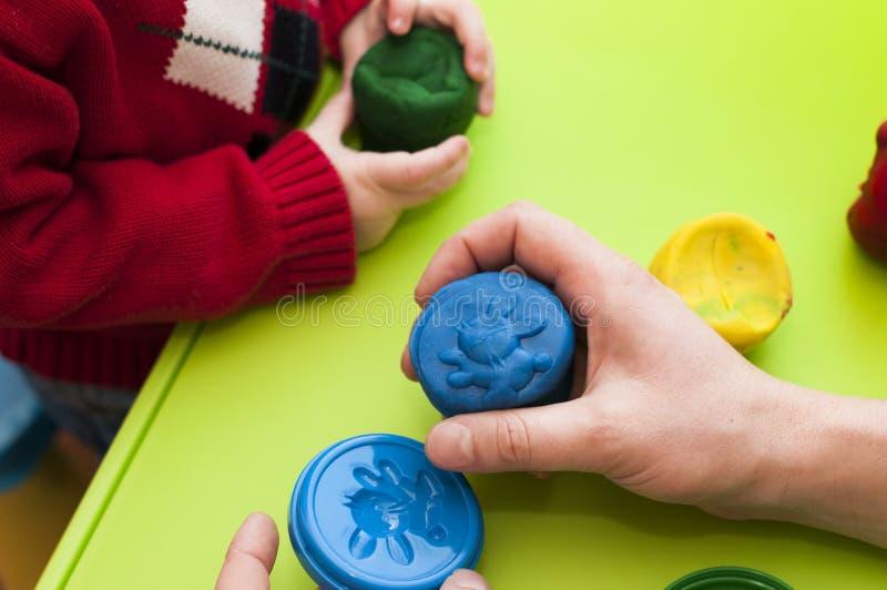 Ein Kind mit einem Mentorspiel mit Plasticine lizenzfreies stockfoto