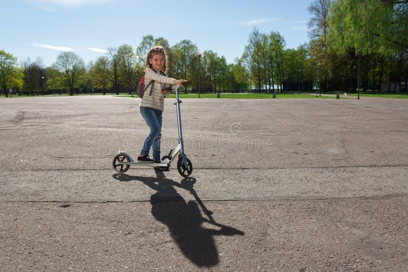 Ein Kind reitet einen Roller lizenzfreies stockfoto