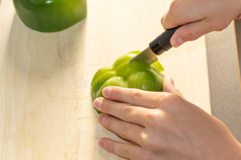 Ein Kind schneidet einen grünen süßen bulgarischen Pfeffer auf einem hölzernen Küchenbrett auf dem Küchentisch stockbild