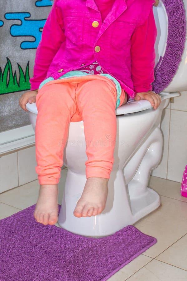 Ein Kind sitzt auf der Toilette lizenzfreies stockbild