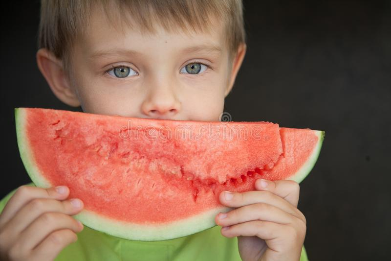 Ein Kind und ein Stück der Wassermelone stockfotos