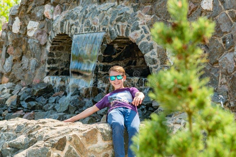 Ein Kind am Wasserfall im Park, ein Junge in der Reserve auf dem Hintergrund des flüssigen Wassers im Park lizenzfreies stockfoto