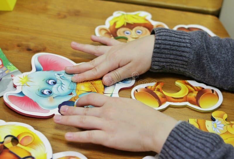 Ein Kind zieht Puzzlespiele lizenzfreie stockbilder