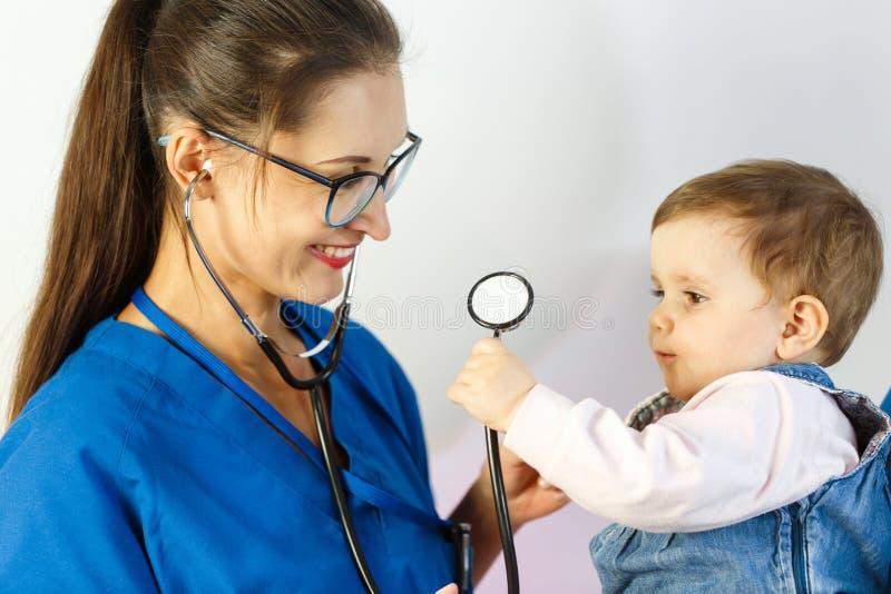 Ein Kinderarzt überprüft ein Kind, während er mit einem Stethoskop spielt Beide lächeln lizenzfreies stockbild