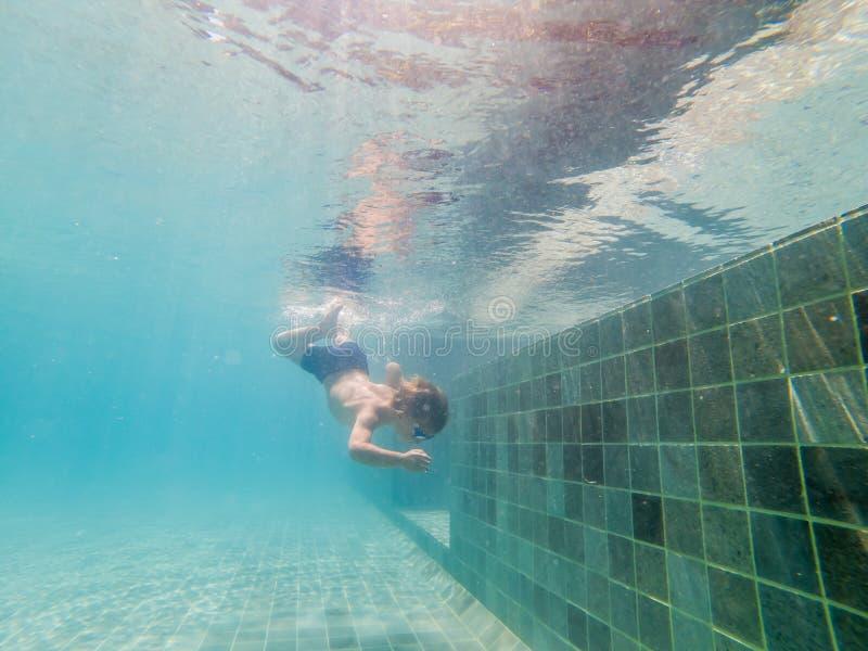 Ein Kinderjunge schwimmt unter Wasser in einem Pool, lächelt und hält Atem, mit schwimmenden Gläsern lizenzfreie stockbilder