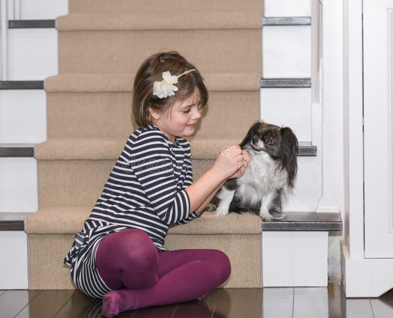 Ein Kinderspiel mit einem Hund innerhalb des Hauses stockfotos