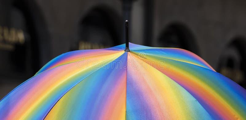 Ein klarer bunter Regenbogenregenschirm gegen einen desaturated dunklen Hintergrund stockbilder