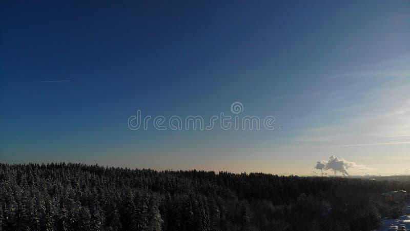 Ein klarer eisiger Tag, den die Sonne Rauch scheint, steigt von den Rohren des Kraftwerks eine Panoramasicht Ausrichtung Russland stockfoto