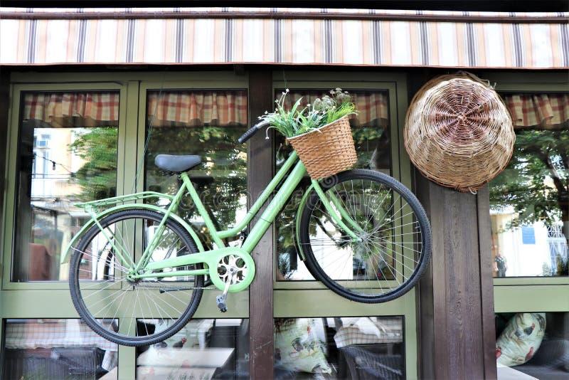 Ein klassisches Fahrrad mit Blumen im Korb, hängend außerhalb eines Fensters lizenzfreie stockbilder