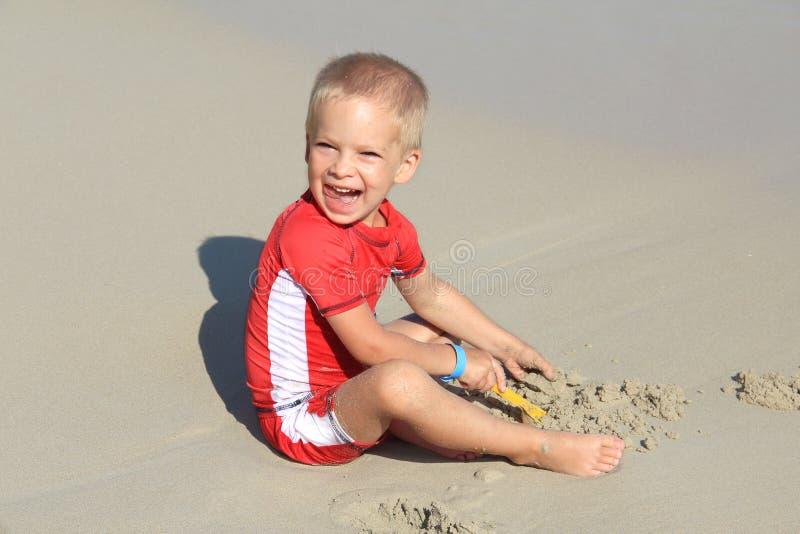 Ein kleiner blonder Junge in der Kleidung mit UV-Filter spielt mit Sand auf dem Strand durch das Meer, Feiertag mit den Kindern u stockbilder