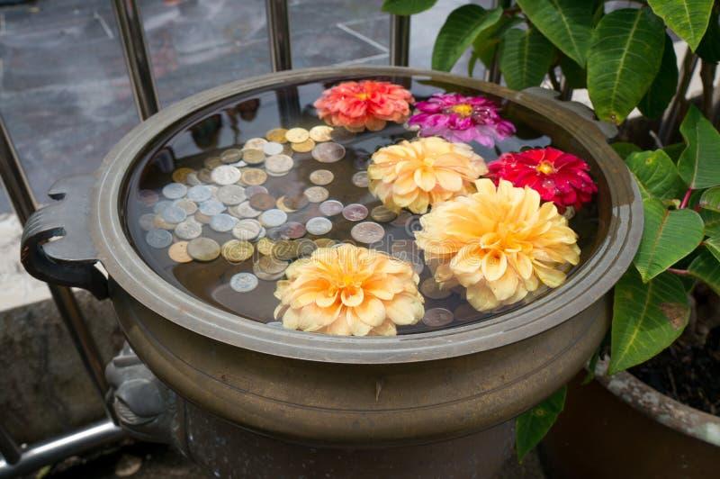 Ein kleiner Blumenwunschbrunnen mit Münzen auf Penang-Hügel stockfoto