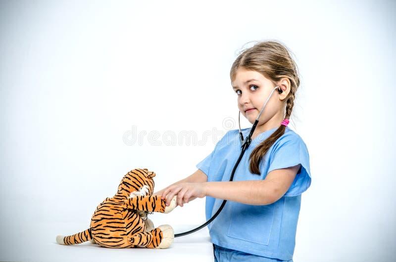 Ein kleiner Doktor hört auf sein Tigerjunges lizenzfreie stockfotos