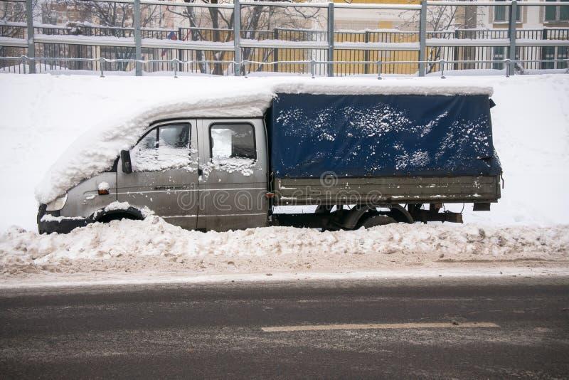 Ein kleiner Frachtzeltpackwagen, bedeckt mit starker Schneeschicht und Schlamm, auf der Fahrbahn lizenzfreie stockfotografie