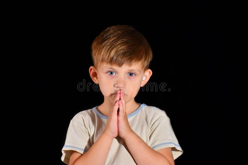 Ein kleiner Junge betet zum Gott mit seinem Hände verstauten offenen mit seinen offenen Augen lizenzfreies stockfoto