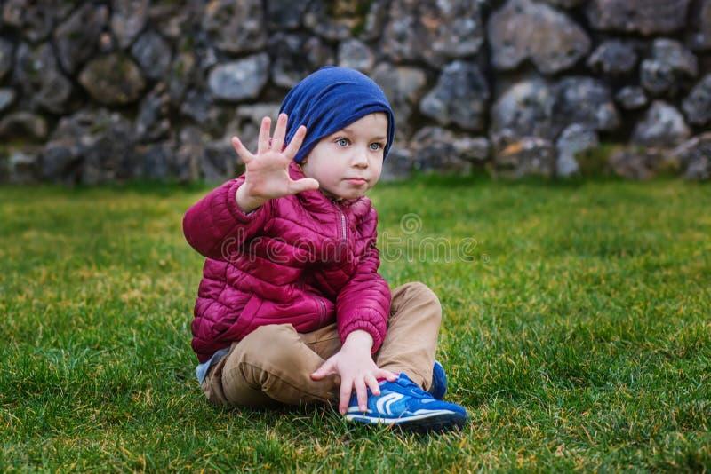 Ein kleiner Junge, der auf dem Gras sitzt stockbild