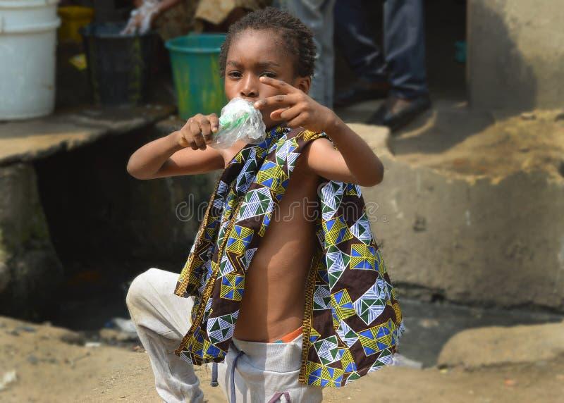 Ein kleiner Junge, der am heißen Nachmittag in Lagos Nigeria 2016 seine Eiscreme genießt stockbilder