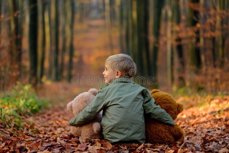 Ein kleiner Junge, der im Herbstpark spielt lizenzfreies stockbild