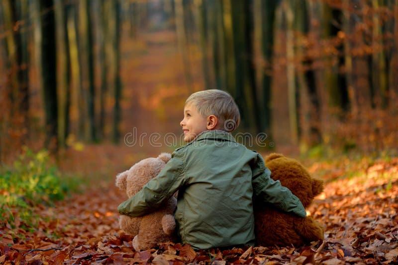 Ein kleiner Junge, der im Herbstpark spielt lizenzfreies stockfoto