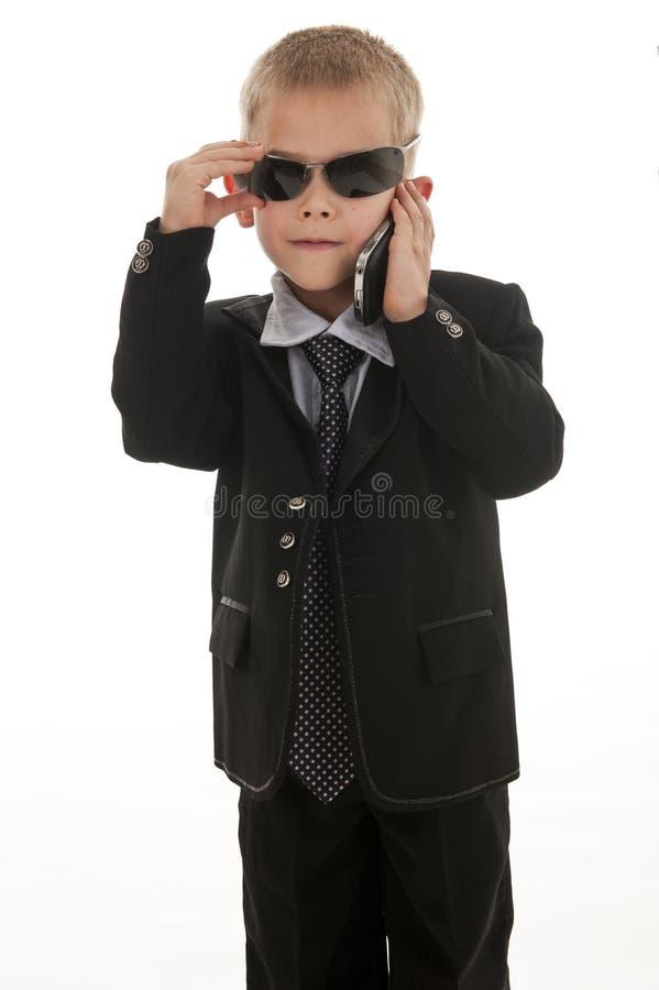 Ein kleiner Junge, der vortäuscht, ein Geschäftsmann zu sein. lizenzfreie stockfotos