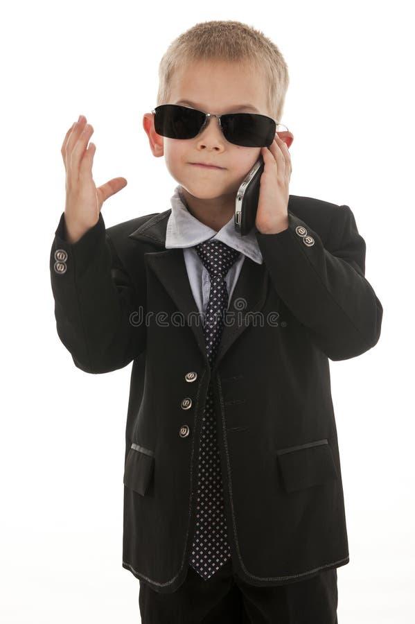Ein kleiner Junge, der vortäuscht, ein Geschäftsmann zu sein. lizenzfreie stockbilder