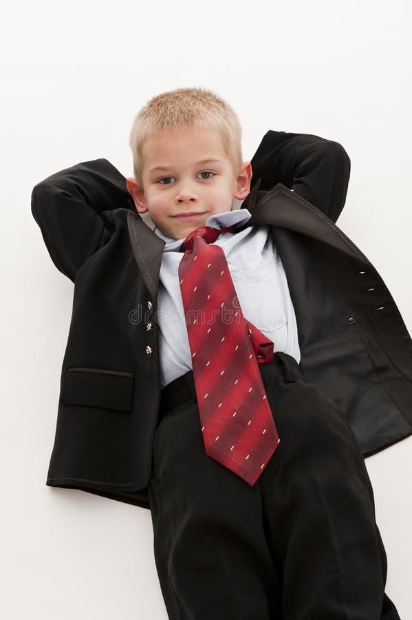Ein kleiner Junge, der vortäuscht, ein Geschäftsmann zu sein. stockfotos