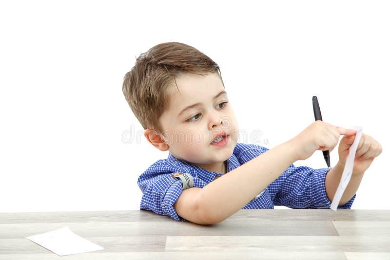 Ein kleiner Junge des Vorschulalters zeigt ein Blatt, auf dem er etwas schrieb oder malte stockbild