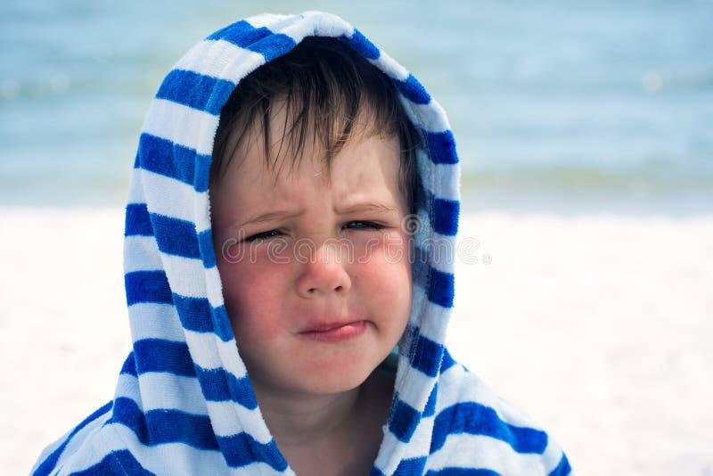 Ein kleiner Junge in einem gestreiften Bademantel an der Küste mit atopic Dermatitis verzog sehr nett und lustig Gesicht, stockbilder