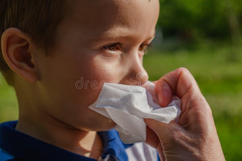 Ein kleiner Junge isst eine Eiscreme im Park und wischt seinen Mund mit einer Serviette ab stockfotos