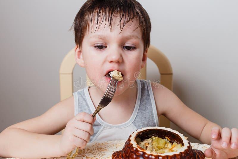 Ein kleiner Junge isst gebackenes Huhn mit Kartoffeln von einem Tongefäß stockbild
