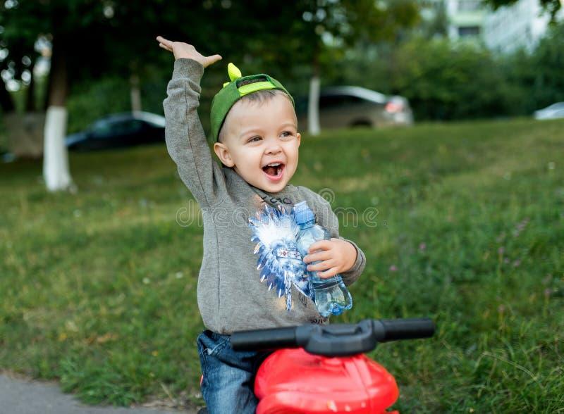 Ein kleiner Junge ist 2-3 Jahre, Kind sitzt auf einem Spielzeug alt In seiner Hand hält eine Flasche Wasser, glückliche Rufe In d lizenzfreies stockfoto