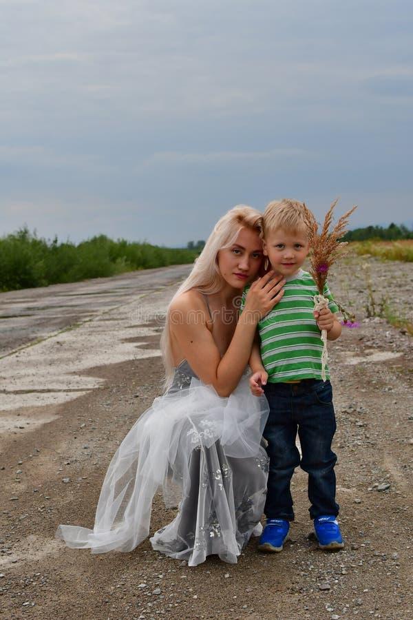 Ein kleiner Junge mit der blonden Stellung seiner Mutter auf dem Gebiet auf der Rollbahn lizenzfreies stockfoto