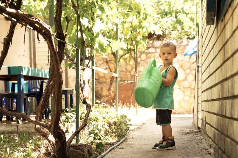 Ein kleiner Junge mit einer großen grünen Gießkanne ist im Yard Der Helfer der großen Mutter lizenzfreie stockbilder