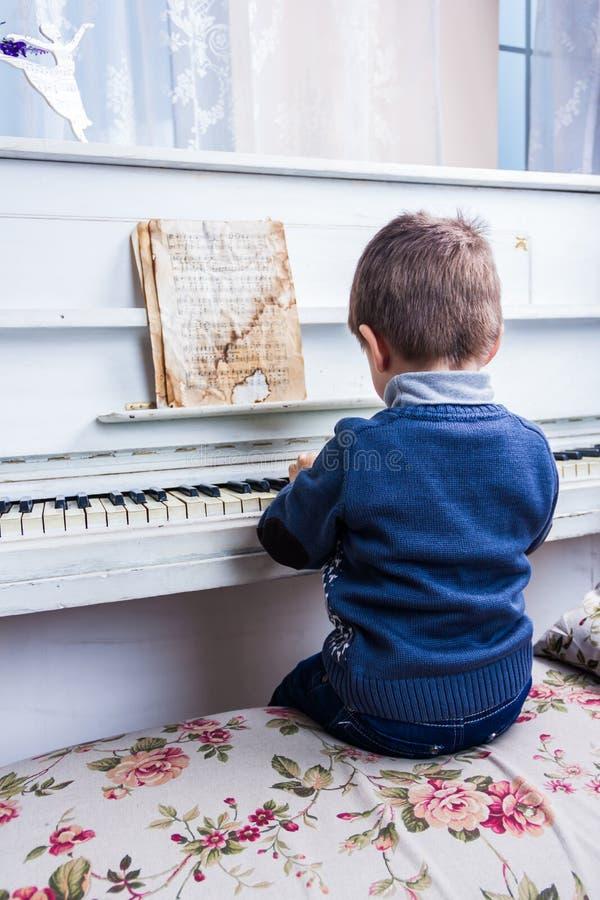 Ein kleiner Junge sitzt am Klavier lizenzfreie stockfotos