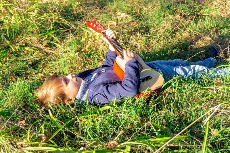 Ein kleiner Junge spielt Gitarre, während er im Park auf grünem Gras liegt stockbild