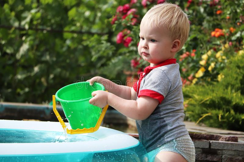Ein kleiner Junge spielt mit Wasser nahe einem aufblasbaren Pool Sommer und Familienurlaube Glückliche Kindheit lizenzfreie stockfotos
