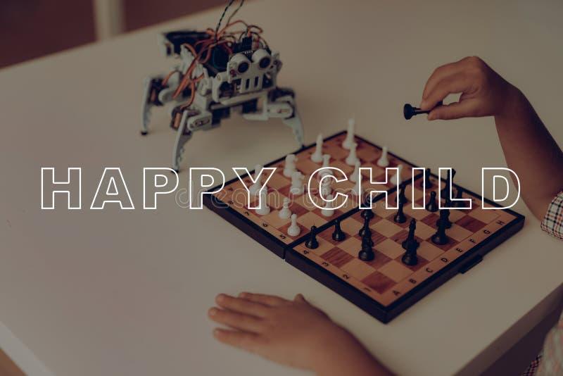 Ein kleiner Junge spielt Schach mit einem grauen Roboter stockfotografie