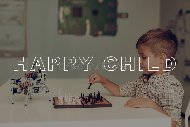 Ein kleiner Junge spielt Schach mit einem grauen Roboter stockfoto