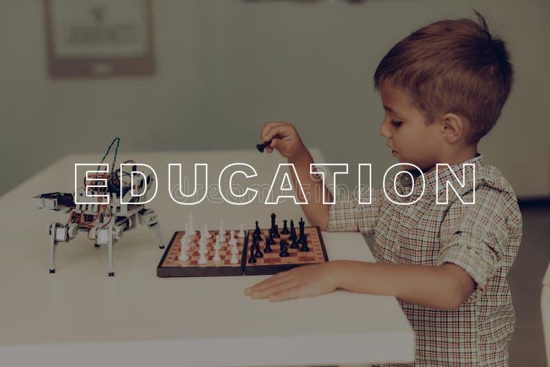Ein kleiner Junge spielt Schach mit einem grauen Roboter stockbilder