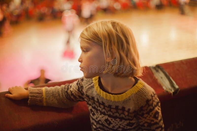 Ein kleiner Junge starrt unten einige Ballsaaltänzer an stockfotografie
