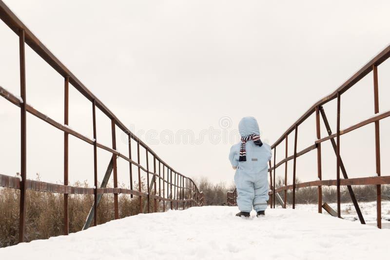 Ein kleiner Junge steht auf einer schneebedeckten Brücke über dem Fluss Das Konzept der Einsamkeit und des Aufgebens stockbild
