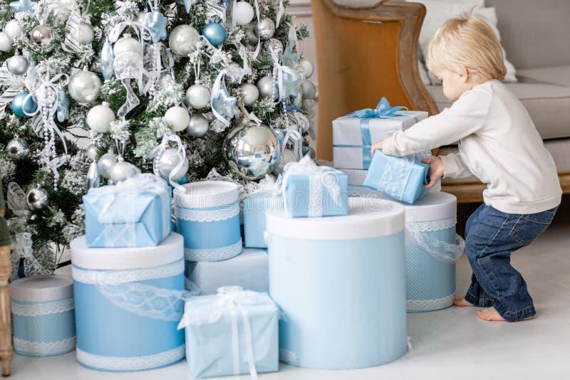 Ein kleiner Junge steht nahe vielen Geschenken Glückliches neues Jahr Verzierter Weihnachtsbaum Weihnachtsmorgen im hellen Leben stockfotografie