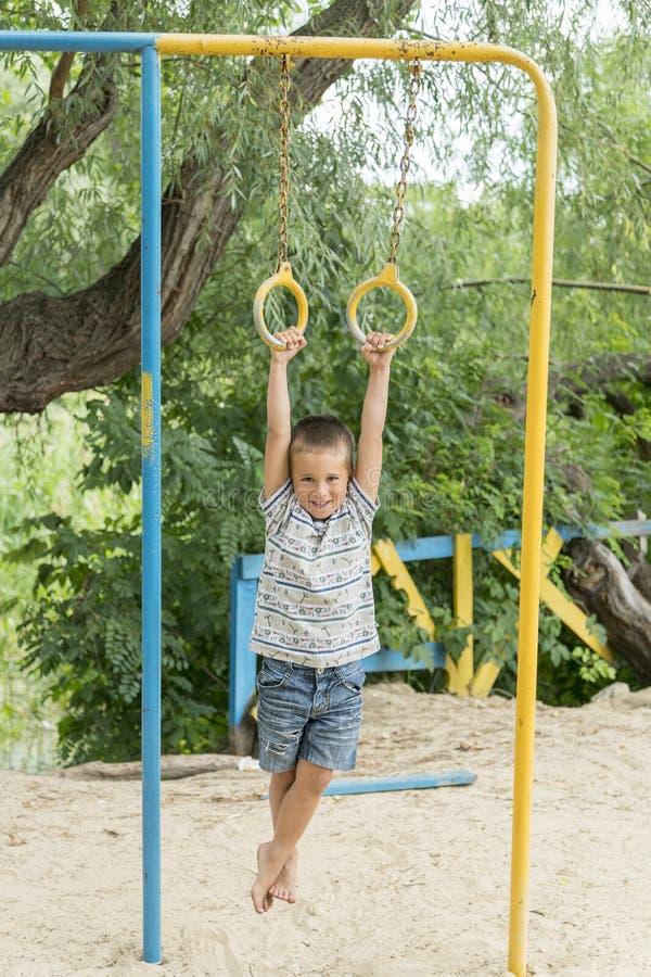Ein kleiner Junge tut phisical Übungen auf einem Sportsground stockfotografie