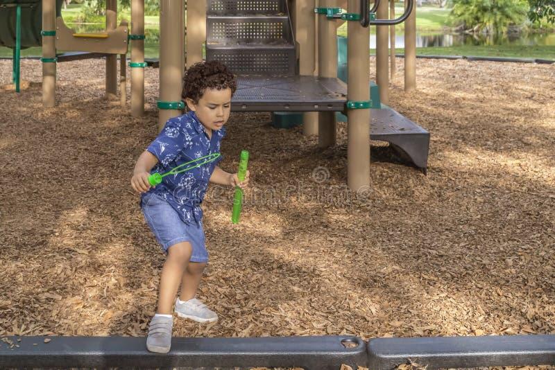 Ein kleiner Junge verlässt den Spielplatz mit seinem Blasenseifenstab lizenzfreie stockfotos