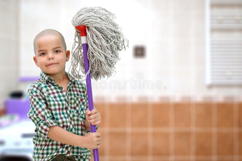 Ein kleiner kahler Junge in einem karierten Hemd auf einem unscharfen Hintergrund des Badezimmers steht mit einem MOPP in seinen  stockfotos