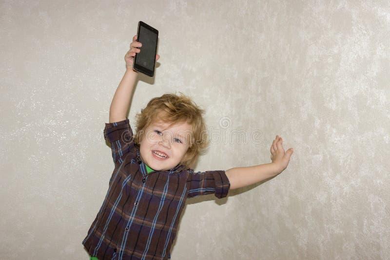 Ein kleiner Kleinkindjunge hebt ein Smartphonegerät über seinem Kopf auf lizenzfreie stockbilder