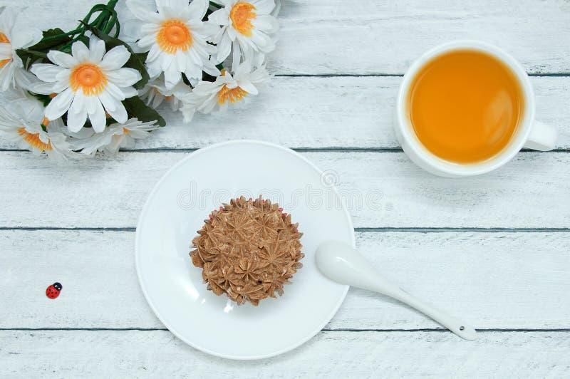 Ein kleiner Kuchen auf einer weißen Platte, eine Schale grüner Tee, ein Bündel Gänseblümchenblumen lizenzfreies stockfoto