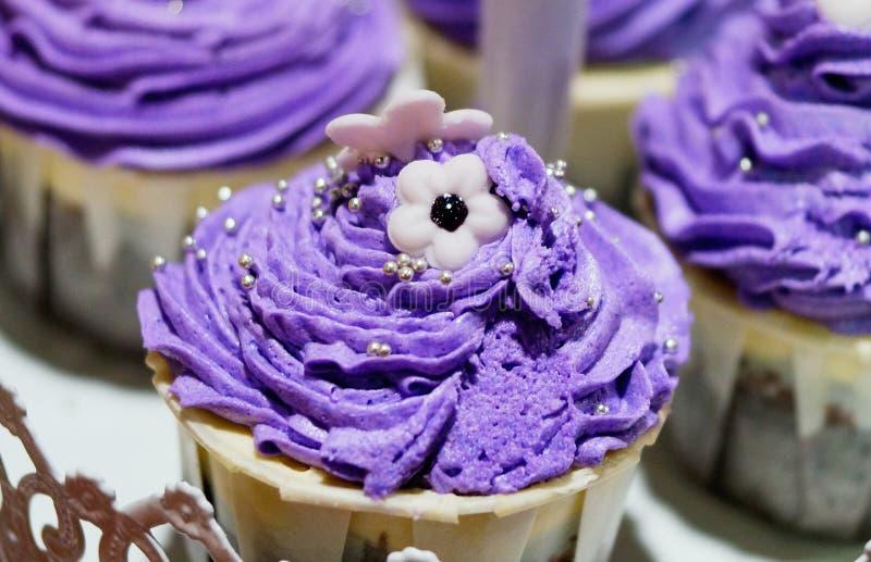 Ein kleiner Kuchen und eine purpurrote Creme auf die Oberseite stockfotografie