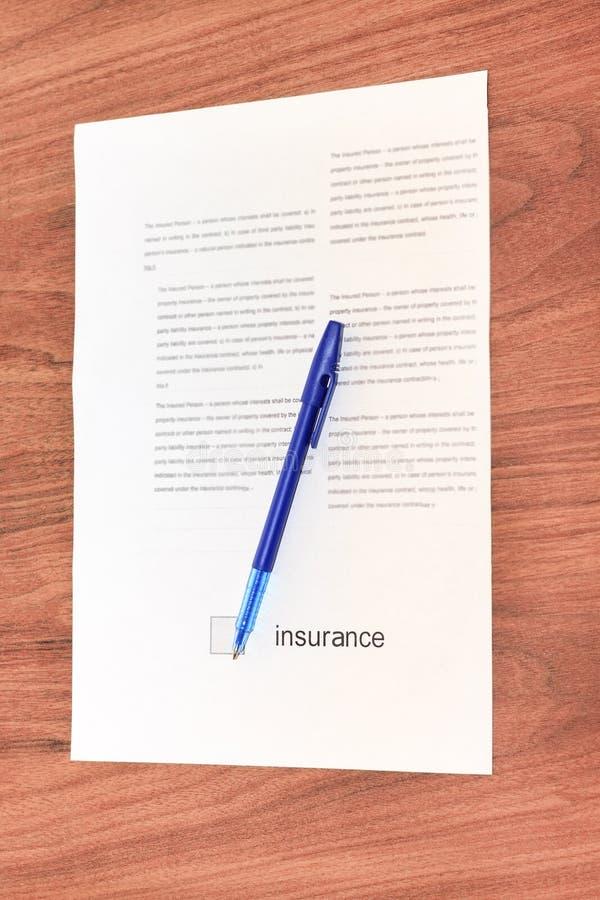 Ein kleiner Pappverschluß in einem alten Design und in einem blauen Griff mit einem Vertrag für Versicherung auf einem hölzernen  stockbild