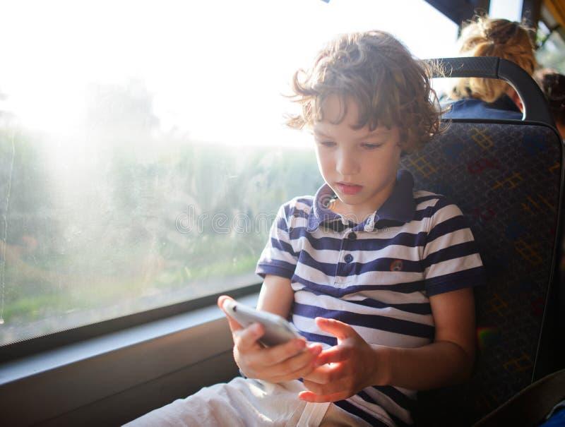 Ein kleiner Passagier eines Stadtbusses mit einem Smartphone in der Hand stockfotografie